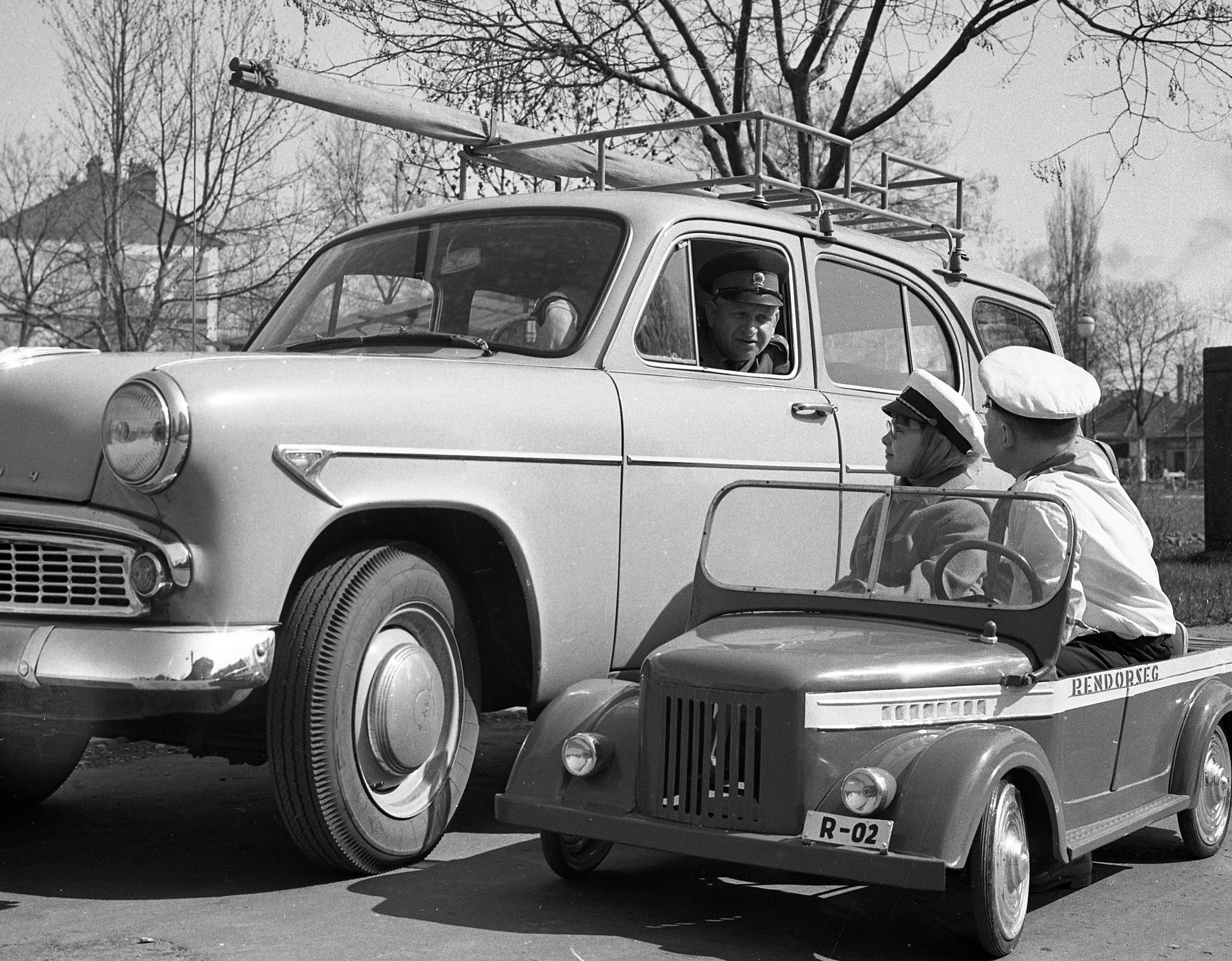 children in toy police car talk to policeman